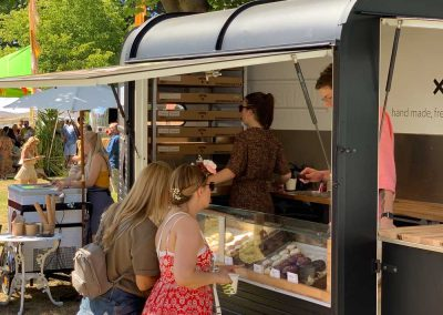 People looking at doughnuts on display in a doughnut truck